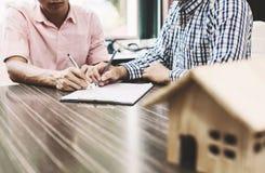 Assinatura de um contrato dos bens imobiliários entre o comprador e o corretor imagens de stock royalty free