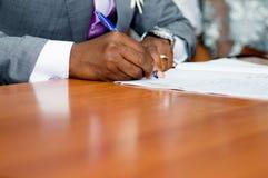A assinatura do noivo nos documentos da união imagens de stock