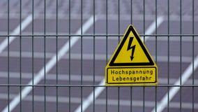 Assine com a alta tensão das palavras - perigo à vida no alemão na frente dos painéis solares Fotografia de Stock Royalty Free