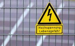 Assine com a alta tensão das palavras - perigo à vida no alemão na frente dos painéis solares imagem de stock royalty free