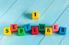 Assine 1º de setembro em cubos de madeira da cor com luz Foto de Stock Royalty Free