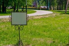 Assine em um quadro do metal no gramado perto da estrada no campo Foto de Stock