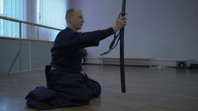 Assis sur le plancher, le samouraï connaît l'épée de katana, puis les hausses et l'attache à la hanche et se lève aux pieds banque de vidéos