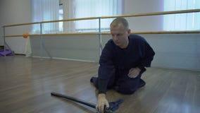 Assis sur les samouraïs de plancher dans le kimono se trouve sur l'épée katan du ` s de Paul dans des couteaux banque de vidéos