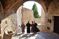 ASSISI, ИТАЛИЯ - 22-ое июля 2017 Монахи идя вдоль улицы старого Assisi в Умбрии стоковое изображение