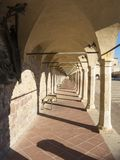 Assisi, Italy. The colonnade of the lower square of the Basilica and the Sacred Convent of Saint Francis royalty free stock photo