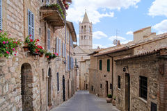 Assisi street. Narrow medieval street in the hill town of Assisi with the church of St Clare in the background royalty free stock images