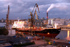 Assist the shipyard cranes. Ship class facing after the renovation of the Gdansk shipyard repair Royalty Free Stock Image