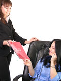 Assistance. An office scenario, an assistant brings some files to the manager royalty free stock photography