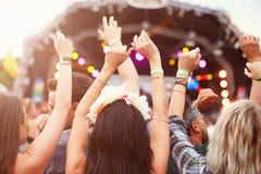 Assistance avec des mains dans le ciel à un festival de musique Images stock