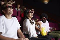 Assistance dans le cinéma portant les lunettes 3D observant le film de comédie images libres de droits