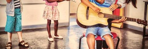 Assistance de professeur enfants pour jouer un instrument de musique dans la salle de classe photo libre de droits