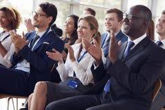 Assistance de sourire applaudissant lors d'un séminaire d'affaires images stock