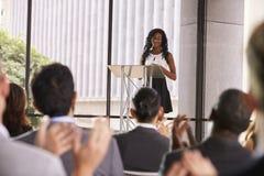 Assistance lors de séminaire applaudissant la jeune femme de couleur au lutrin image stock