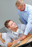 Assistance from senior teacher. Student getting assistance from senior teacher in university class royalty free stock images