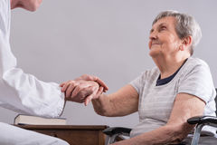 Assistance to elderly. Doctor holding the hand of an elderly woman Royalty Free Stock Photos