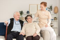 Assistance woman consoling senior couple. Professional assistant supporting and consoling a worried senior married couple in a living room of a day care center stock photo