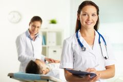 Assistant. Portrait of confident female doctor looking at camera in hospital Royalty Free Stock Images