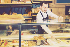 Assistant baker showing cakes. Young assistant baker showing cakes in the shop Royalty Free Stock Photo