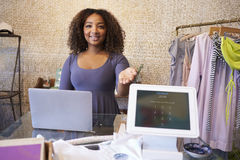 Assistant at clothing store shows computer used for payment Stock Photography