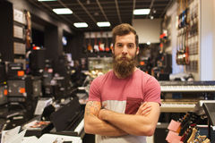 Assistant or customer with beard at music store Royalty Free Stock Photos