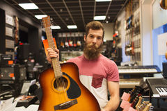 Assistant or customer with guitar at music store Stock Photo