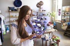 Assistant de boutique à l'aide du comprimé avec des icônes d'APP dans la boutique Photos stock
