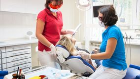 Assistant de dentiste à l'aide de la lampe de traitement dentaire UV sur des dents de patients image libre de droits