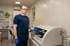 Assistant de laboratoire faire le sang d'essai dans l'analyseur automatique de prise de sang image stock