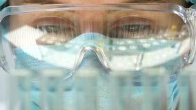 Assistant de laboratoire faisant l'analyse chimique, tubes à essai se reflétant en verres banque de vidéos