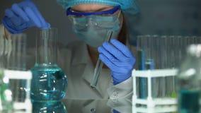 Assistant de laboratoire prélevant l'échantillon provenant du flacon avec le liquide bleu, analyse comparative banque de vidéos