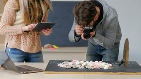 Assistant des coulisses de travail d'équipe de photographe créatif banque de vidéos