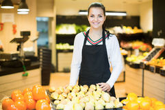 Assistant displaying fruits of grocery store Royalty Free Stock Image
