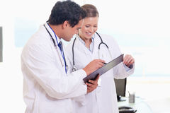 Assistant doctors reading off clip board Stock Image