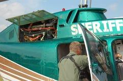 Assistant du shérif s'élevant dans l'hélicoptère de police Image stock