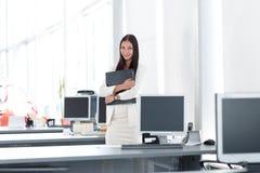 Assistant féminin avec des documents se tenant dans le bureau Photo avec l'espace de copie Image libre de droits