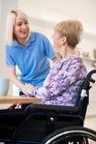 Assistant féminin de soin parlant à la femme supérieure s'asseyant dans le fauteuil roulant à la maison photographie stock libre de droits