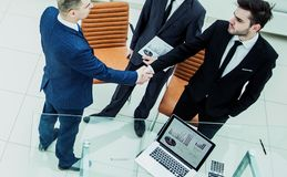 Business partners shake hands before starting a business meeting. Assistant with financial documents and business partners shake hands before starting a business Royalty Free Stock Photography