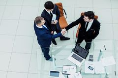 Business partners shake hands before starting a business meeting. Assistant with financial documents and business partners shake hands before starting a business Royalty Free Stock Photo