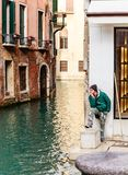 Assistant gondolier in anticipation of  arrival of gondola. Venice Stock Photography