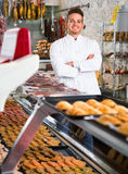 Assistant in grocery shop greeting customers Royalty Free Stock Images