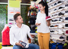 Assistant helping customer to choose sneakers Stock Photography