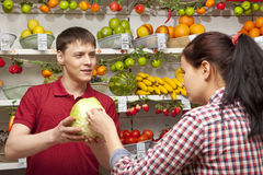 Assistant helping customer at vegetable counter of shop Stock Photography