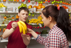 Assistant helping customer at vegetable counter of shop Stock Image