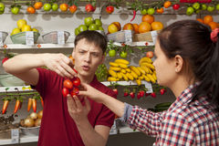 Assistant helping customer at vegetable counter of shop Stock Photos