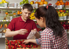 Assistant helping customer at vegetable counter of shop Royalty Free Stock Image