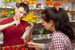 Assistant helping customer at vegetable counter of shop Stock Images