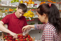 Assistant helping customer at vegetable counter of shop Royalty Free Stock Photo