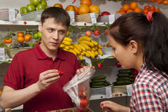 Assistant helping customer at vegetable counter of shop Royalty Free Stock Photos