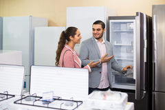 Assistant helping customers to choose. Experienced shop assistant helping happy customers to choose household appliances Stock Photos